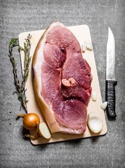 향신료와 절단 칼을 곁들인 생 돼지 고기 조각. 돌 테이블에. 평면도