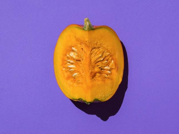 Кусок спелой тыквы при ярком свете на фиолетовом фоне. вкусный и полезный овощ.