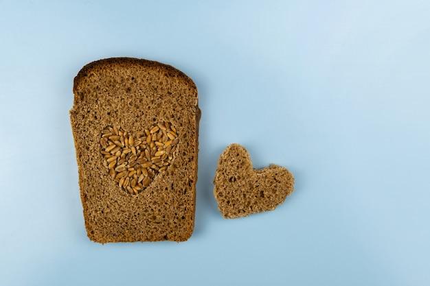 Кусок ржаного хлеба, в центре которого вырезано сердце, посыпанное пшеницей, рядом с сердечком из хлеба.