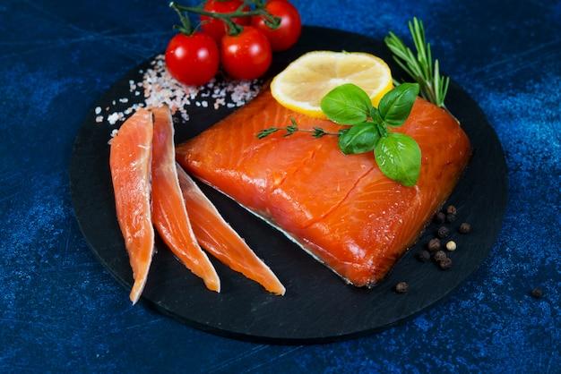 Кусок копченой красной рыбы со специями и травами лежит на черной угольной доске.