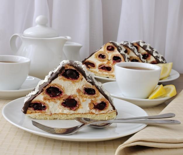 Кусок бисквитного десерта с кремом с вишней в шоколадной глазури и кокосом