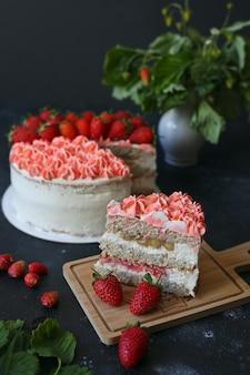 暗いテーブルの上にイチゴとスポンジのクリーミーなケーキの一部