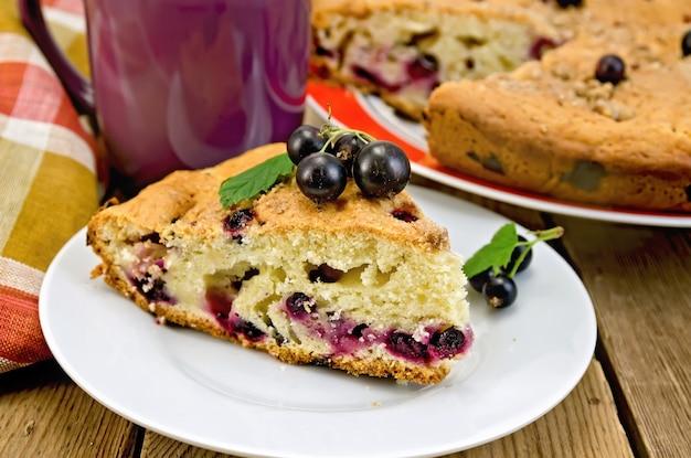 木の板の背景に黒スグリ、ナプキン、カップと甘いケーキの一部