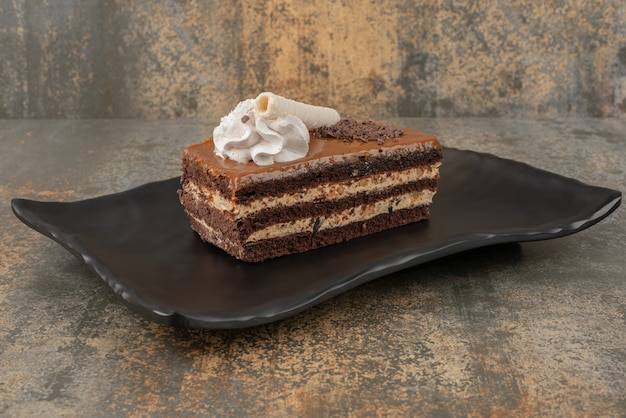 Кусок сладкого пирога на темной тарелке