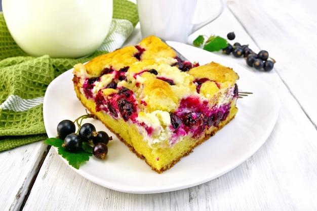 黒すぐりのベリーと皿の上のフォーク、ナプキン、軽い木の板に対するガラスの水差しのミルクと甘いパイの部分