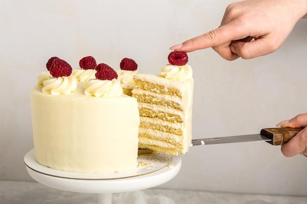 Кусок белого торта со сливками и малиной, в руке женщины, на металлической лопатке, сером фоне. выборочный фокус.