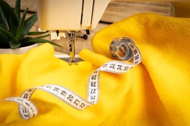 Кусок желтой ткани на швейной машинке и сантиметр на деревянном фоне