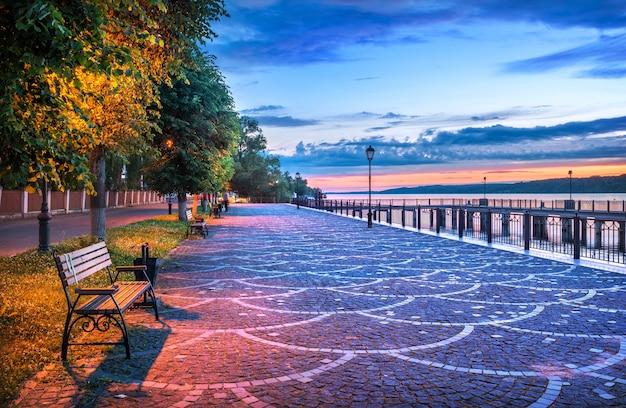 夏の夜のプライオメトリックスのヴォルガ堤防の桟橋と木の近くのベンチ