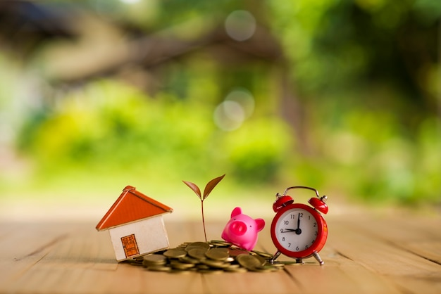 ピギーバンクは、スタッキングゴールドコインと黒板の家を置き、ヴィンテージの青色の背景に時計を入れ、将来のコンセプトに計画された投資のために新しい不動産やローンを購入するためのお金を節約します。