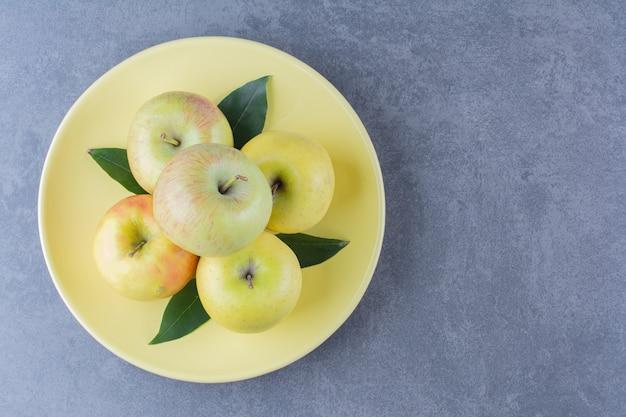Куча яблок на тарелке на темной поверхности