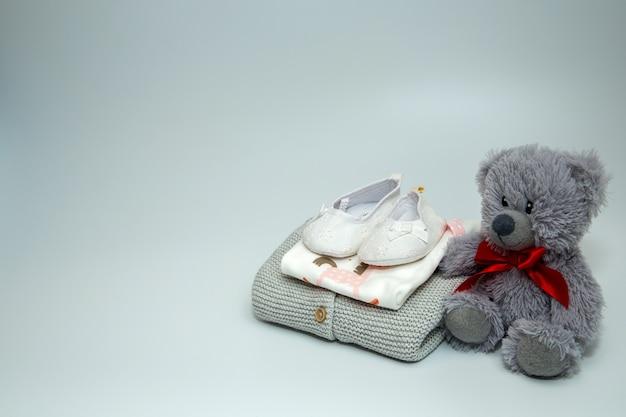 테디 베어와 함께 아기 옷과 액세서리 더미