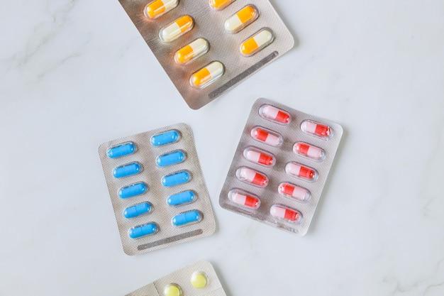 さまざまな錠剤や医療用カプセルが入ったブリスターパックの山