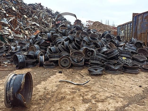 재활용 및 재용해를 위해 운송할 준비가 된 폐차장에 있는 부서진 마모된 자동차 테두리 더미