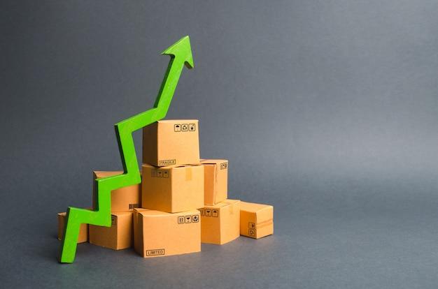 골 판지 상자 및 녹색 위쪽 화살표의 더미. 상품 및 제품 생산의 성장률