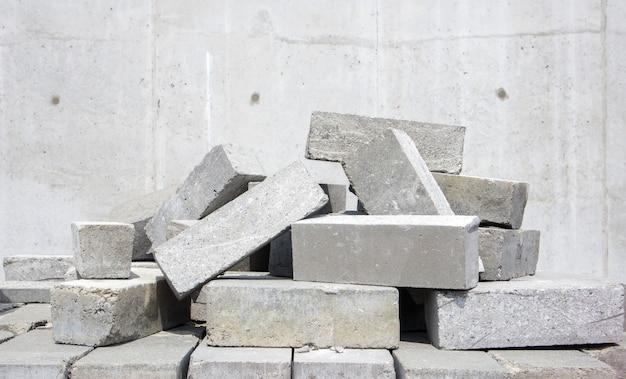 Куча из кирпича цементного типа. для строительства используется полнотелый кирпич. на стройплощадке много рыхлого бетонного кирпича.