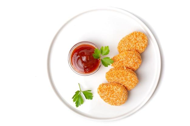 Куча приготовленных куриных наггетсов в тарелке с томатным соусом, изолированные на белом фоне