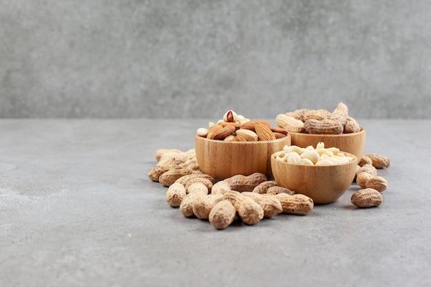 Куча разных видов орехов в мисках рядом с разбросанными арахисами на мраморном фоне. фото высокого качества