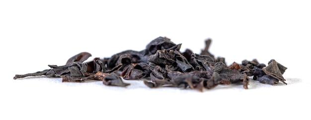 Куча сушеных листьев черного чая на белом. энергетический напиток.