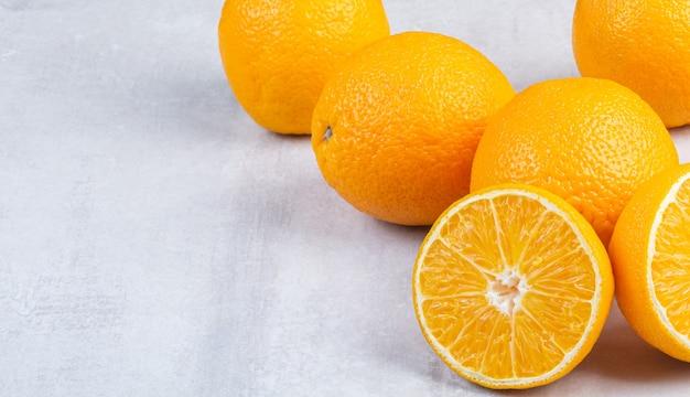 Куча свежих апельсинов на мраморе.