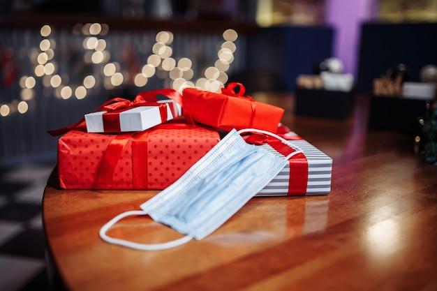 Куча подарочных коробок и медицинской маски на столе в кафе. стопка подарков на деревянной поверхности в ресторане. новый нормальный