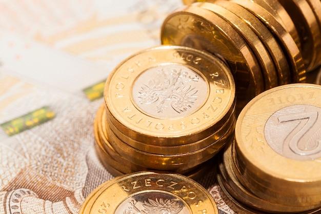 Куча польских монет золотого цвета - злотые, лежащие на новых польских банкнотах, фото крупным планом под углом