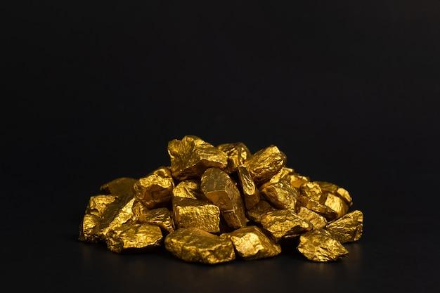 Куча золотых самородков или золотой руды на черном фоне