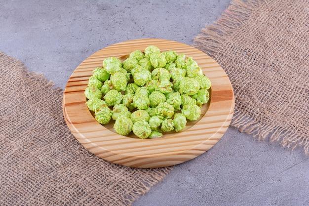 Куча зеленого засахаренного попкорна на деревянном блюде, помещенном поверх кусков ткани на мраморном фоне. фото высокого качества
