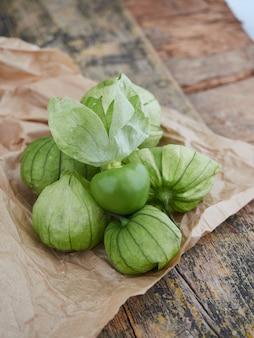 소박한 나무 테이블에 포장지에 녹색 tomatillo 과일 더미
