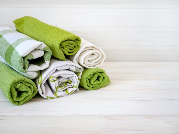 나무 배경에 깔끔하게 접힌 수건 더미. 천연 섬유 섬유 생산. 유기농 제품. 천연 소재.