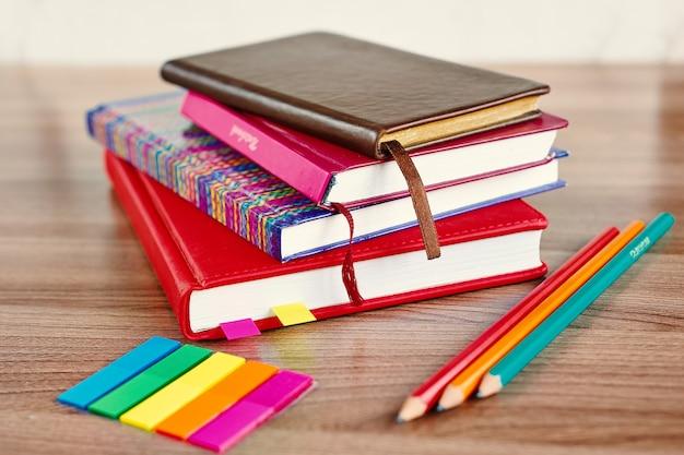 木製のテーブルに鉛筆と色のブックマークが付いたメモ帳の山