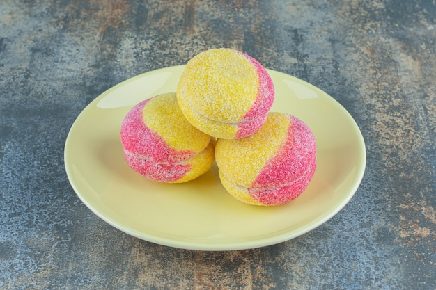 Куча печенья в форме персика на тарелке, на мраморной поверхности.