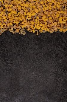 복사할 공간이 있는 어두운 구조적 배경에 격리된 원시 노란색 파스타 더미