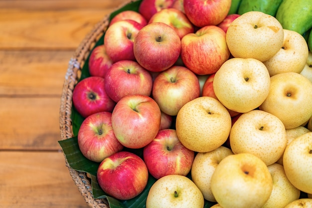 Куча красного яблока и желтой китайской груши от верхнего взгляда стола на бамбуковой плетеной пластине и деревянном столе.