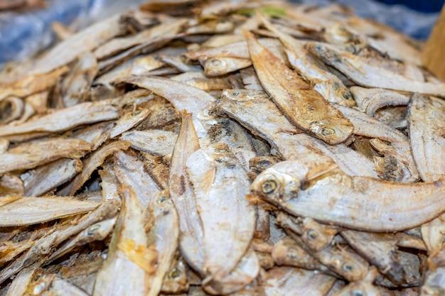 짠 말린 바다 물고기 더미는 선별적인 초점으로 시장을 가까이서 볼 수 있습니다