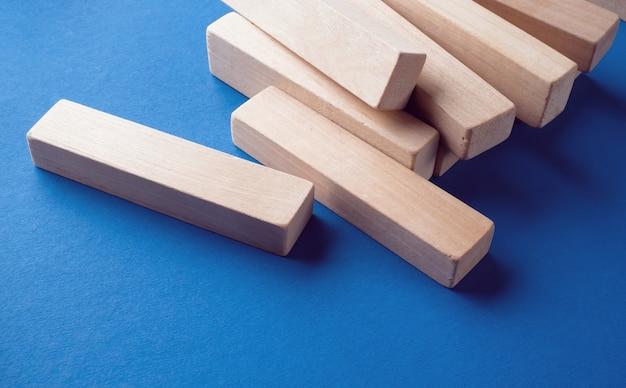 青色の背景に散在した木製のブロックの山。建設ゲーム。壊れた塔。