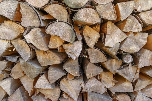 Куча сложенных дров. дрова заготовленные для отопления зимой. колотые дрова в стеке.