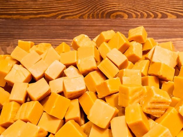 立方体の形のオレンジ色のタフィーのお菓子の山は、おいしいお菓子の背景を抽象化します
