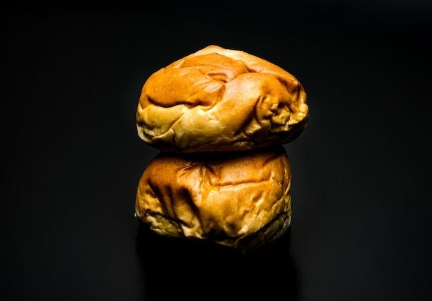 어두운 배경에 두 개의 맛있는 버거 빵 더미