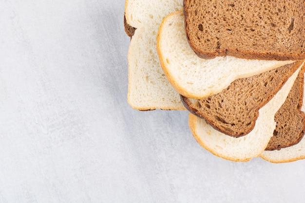 大理石の背景に、さまざまなスライスされたパンの山。