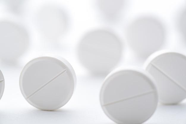 明るい白い表面に散らばった白い錠剤の山。セレクティブフォーカス。