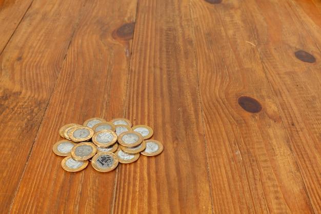 Куча с большим количеством реальных бразильских денежных монет на деревянном столе