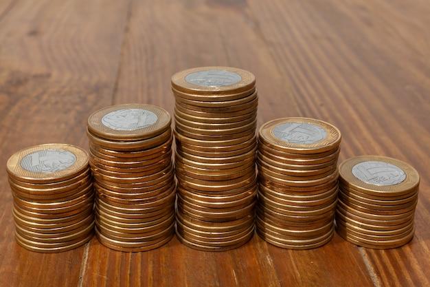 Куча с большим количеством настоящих бразильских денежных монет, сложенных в виде гистограммы на деревянном столе
