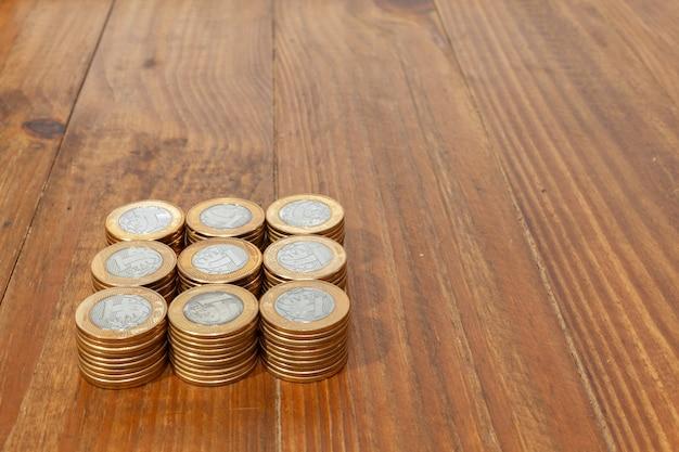 Куча настоящих бразильских денежных монет на деревянном столе