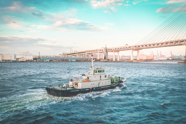 パイロット船またはタグボートが横浜の大きなクルーズ船を海に向けて案内しています。