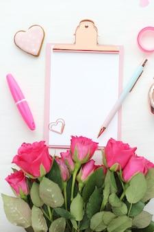 白い紙、ペーパークリップ、白いテーブルにピンクとブルーのペン、ジンジャーブレッドのハート、明るいピンクのバラの花束が付いたピンクとゴールドのクリップボード。フラットなレイアウト、トップビュー。