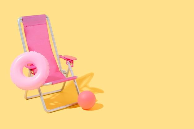 Розовый шезлонг с поплавком и мячом на желтом фоне лето и путешествия 3d иллюстрация