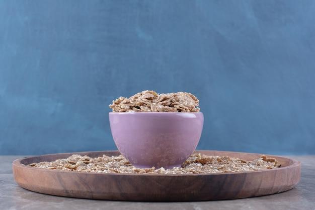 나무 판자에 아침 식사로 바삭바삭한 건강 시리얼로 가득 찬 분홍색 그릇.