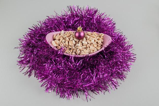 クリスマスボールと健康的なシリアルがいっぱいのピンクのボウル。