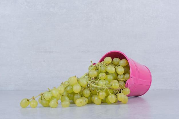 녹색 달콤한 포도로 가득한 분홍색 양동이. 고품질 사진