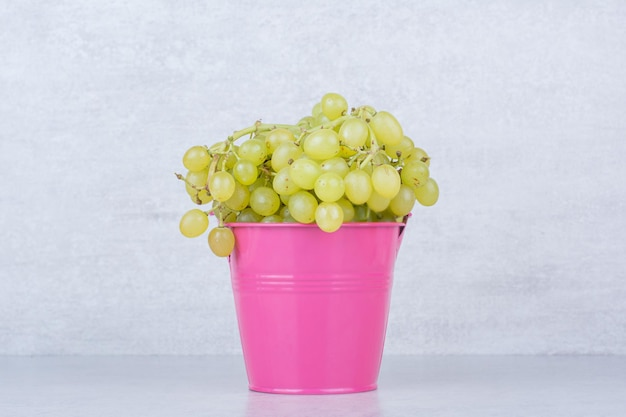 緑の甘いブドウでいっぱいのピンクのバケツ